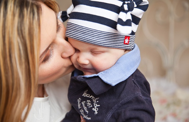 woman kissing kid